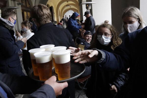 Ľudia s ochrannými rúškami stoja v rade na pivo na letnej terase reštaurácie v Prahe.