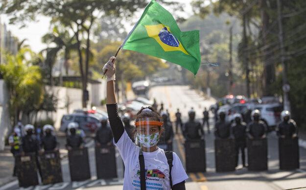 Obyvateľka Paraisopolisu, jedného z najväčších slumov v Brazílii, máva vlajkou a žiada politikov, aby v súvislosti s pandémiou ochorenia COVID-19 venovali slumom väčšiu pozornosť.