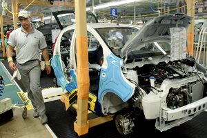 Robotník nastavuje brzdy na Citroene C1 v továrni TPCA v Kolíne pri Prahe.