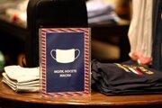 """Tabuľka s nápisom """"Prosím, noste rúška"""" na stole s tričkami v jednom z obchodov v nákupnom centre v bulharskej Sofii 18. mája 2020."""