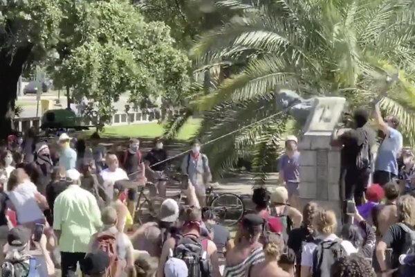Demonštranti zhadzujú sochu Johna McDonogha v sobotu 13. júna 2020 na Duncan Plaza v New Orleans. Foto: SITA/AP