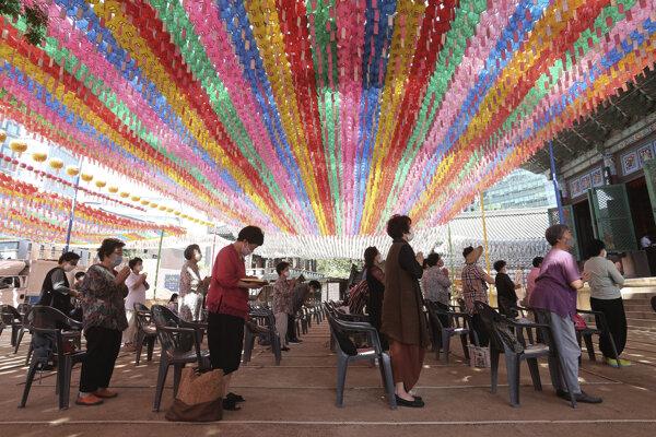 Ľudia s ochrannými rúškami počas modlitby v chráme Chogyesa v Južnej Kórei 22. júna 2020.