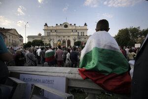 Mladý demonštrant s národnou vlajkou protestuje pred parlamentom v centre Sofie.