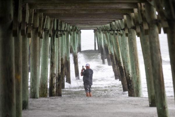 Muž sleduje vlnobitie a začiatok hurikánu v Garden City v Severnej Karolíne.