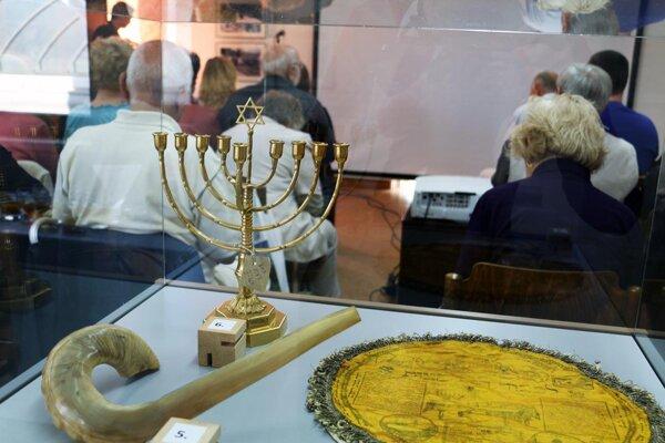 Vystavené rituálne predmety v pozadí osemramenný svietnik, v popredí vľavo hudobný nástroj z baranieho rohu a vpravo vrecko na macesy.