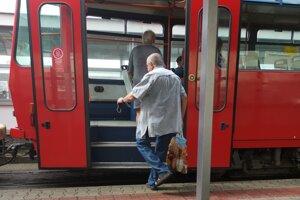 Cestujúci nastupuje do MHD s rúškom v ruke, nie na tvári