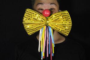 Divadelný kostýmový návrhár a herec Edmond Kok pózuje s ochranným rúškom, ktoré vytvoril z klaunovho nosa a mašle.