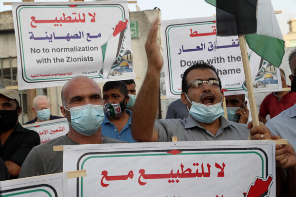 """Účastníci protestov mali v rukách palestínske vlajky a plagáty s nápismi: """"Zrada"""", """"Nie normalizácii so židovským okupantom"""", či """"Zmluvy hanby""""."""