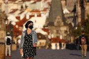 Žena s ochranným rúškom kráča po Karlovom moste v Prahe.