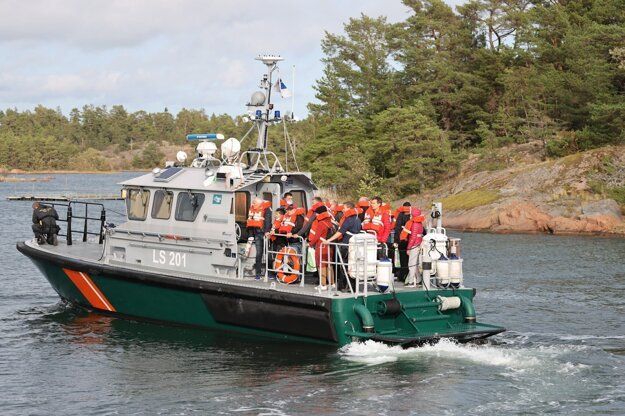 Fínska pobrežná stráž evakuuje ľudí z uviaznutého plavidla.