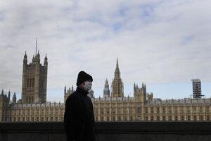 Muž s ochranným rúškom na tvári kráča okolo parlamentu v Londýne počas koronavírusovej pandémie 16. októbra 2020.