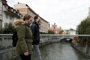 Ľudia s ochrannými rúškami kráčajú po moste cez rieku Ľubľanica v centre slovinskej metropoly Ľubľana.