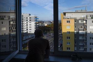 Muž sa pozerá na ulicu z okna bytu v bratislavskej mestskej časti Podunajské Biskupice.