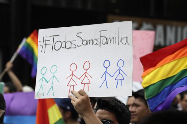 """Muž drží transparent s nápisom """"My všetci sme rodina"""" počas demonštrácie v Mexico City."""