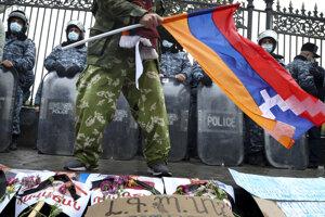 Demonštrant s arménskou vlajkou pred policajtmi na proteste v Jerevane.