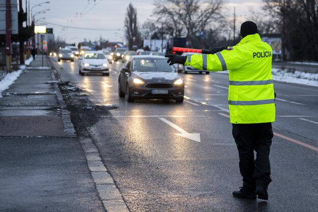 Policajt zastavuje vodiča auta počas kontroly dodržiavania protipandemických opatrení na Gagarinovej ulici v Bratislave.