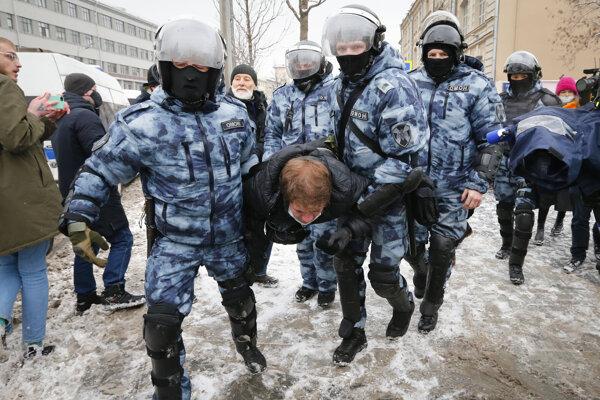 Polícia odnáša demonštranta na proteste v Moskve.
