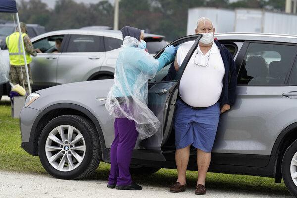 Muž dostáva vakcínu počas očkovania proti ochoreniu COVID-19 na outdoorovom vakcinačnom mieste v meste Bradenton na Floride.