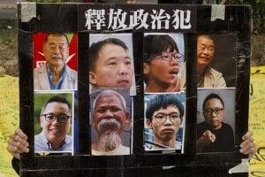 Demonštrant s fotografiami hongkongských aktivistov.