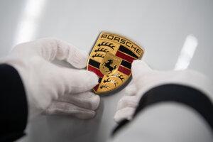 Zamestnankyňa Volkswagenu umiestňuje logo na auto Porsche Taycan.