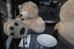 Plyšové medvede z kníhkupectva Philippa Labourela sedia za stolmi v reštaurácii v Paríži.