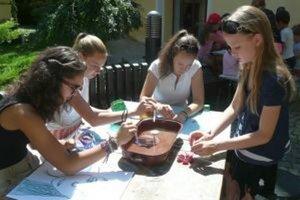 Prázdninové maľovanie na nádvorí galérie - deti si s Elenou Tarábkovou (vľavo) pripravujú zmes olejovej farby, benzínu a vody.