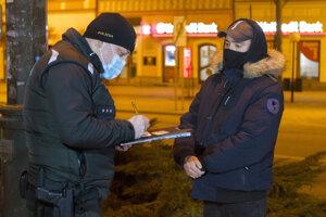 Policajt kontroluje dodržiavanie nočného zákazu vychádzania.