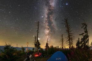 Mliečna cesta a protisvit (naľavo) počas teplej letnej noci pod hviezdnou oblohou.