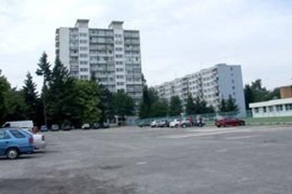 Pohľad na časť parkoviska na Chrenovej, kde majú vyrásť domy. Vpravo je atletický štadión.
