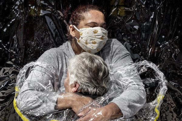 Fotografia s názvom Prvé objatie od dánskeho fotoreportéra Madsa Nissena, ktorá vyhrala v celkovom hodnotení tohtoročnú prestížnu súťaž World Press Photo, zachytáva prvé objatie 85-ročnej Brazílčanky Rosy Luzie Lunardiovej a jej ošetrovateľky cez plastovú mebránu po piatich mesiacoch v domove dôchodcov v Sao Paule.
