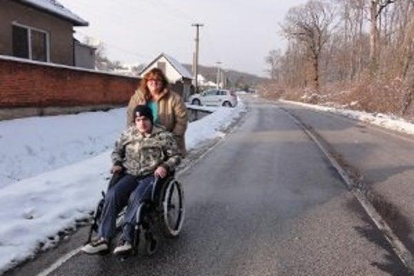 Vozičkár Jozef Augustín nemá inú možnosť, ako zísť na cestu, ak sa chce z domu niekam dostať - chodníkov v časti Topoľčianok, kde býva, niet. Na snímke je Jozef s mamou Lýdiou.