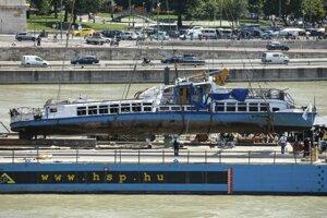 Na archívnej snímke z 11. júna 2019 žeriav kladie vrak výletnej lode Hableány na pontón po vytiahnutí z vody pri Margitinom moste na rieke Dunaj v Budapešti.