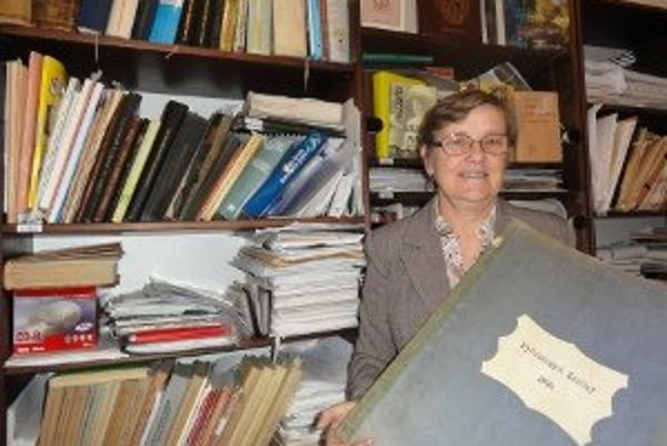 Riaditeľka archívu Šarlota Drahošová so zväzkom novín z roku 1899.
