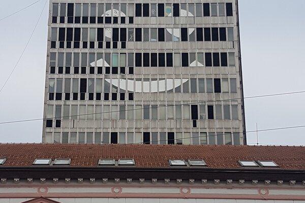Na ošarpanej výškovej budove na Garbiarskej ulici vytvárajú papiere obrovského smajlíka.