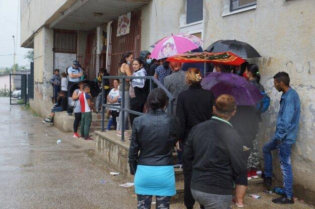 Neďaleko miesta očkovania stála na daždi fronta čakajúcich na sociálne dávky.