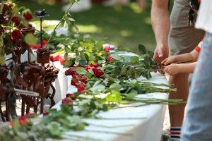 Ľudia kladú ruže pri katedrále v Osle ako prejav úcty voči obetiam útokov z roku 2011.