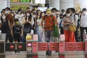 Ľudia kráčajú na železničnej stanici v Tokiu.