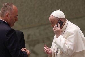 Pápež František telefonuje mobilom, ktorý mu podal jeho komorník Piergiorgio Zanetti po skončení pravidelnej generálnej audiencie v Aule Pavla VI. vo Vatikáne v stredu 11. augusta 2021.