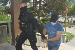 Policajti priviedli obvineného na súd. Tvár si zakrýval šiltom.