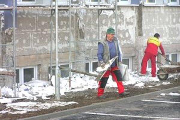 Robotníci odstraňujú z fasády horľavý polystyrén, musia ho nahradiť nehorľavým materiálom.