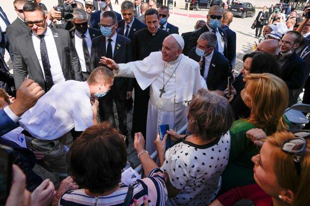 Pápež František požehnáva muža pred katedrálou.