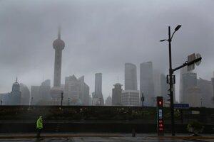 Dopravný policajt stojí v daždi na ulici v čínskom Šanghaji.