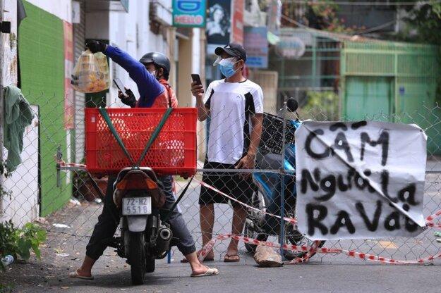 Kuriér podáva jedlo cez plot vo vietnamskom meste Vung Tau.