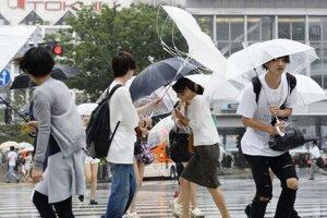 Ľudia kráčajú po ulici v Tokiu počas silného vetra.