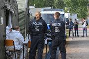 Nemecká polícia čaká na príchod migrantov v centre prijímajúcom žiadateľov o azyl.