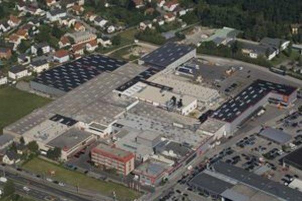 Letecká snímka výrobného závodu v Linzi v Rakúsku z roku 2007. Rodinné domy sú od továrne vzdialené  30 metrov, zásobáreň podzemnej vody 3 kilometre.