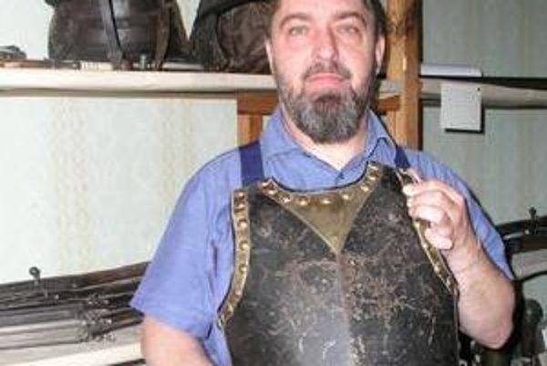 Numizmatik a historik Vladimír Bíroš s náprsným pancierom  z 18. storočia, v pozadí helmy a zbrane.