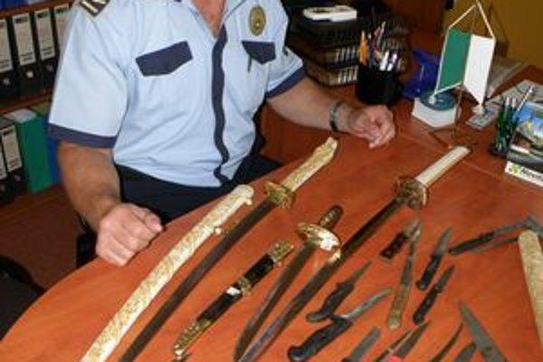 Na stole náčelníka R. Majora sú desiatky zadržaných zbraní. Najväčší meč má asi meter.