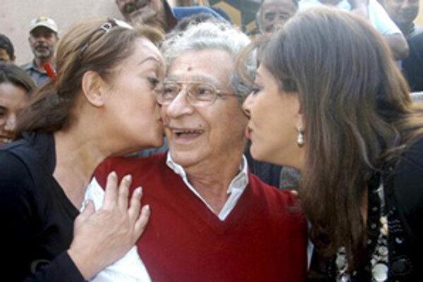 Egyptské herečky Hala Sodqiová (naľavo) a Hala Fakherová dávajú bozk režisérovi Youssefovi Chahinovi.