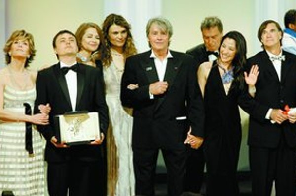 Jane Fondová drží víťaza – rumunského režiséra Cristiana Mungiua. V strede je Alain Delon a vpravo Gus Van Sant.